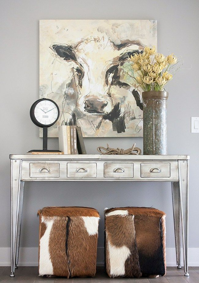 When you're decorating with neutrals adding something unexpected, like these cowhide ottomans, can help spice up your space. Foyer, entry, gray wall, metal console table