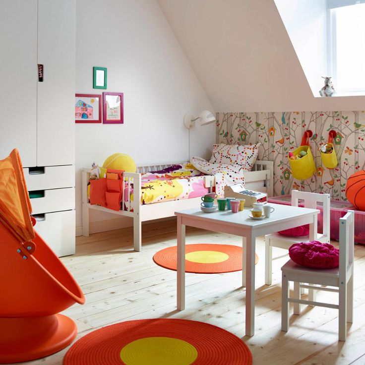 A colourful children's room with a white bed made with colourful quilt cover and pillowcase. Shown with orange/yellow rugs, a children's swivel armchair with hood and a white table with two chairs.