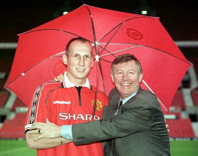 Ferguson poses with new signing Jaap Stam and his umbrella as the rain falls at Old Trafford, May 1998