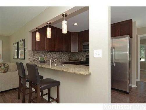 New home - rambler galley kitchen renovation idea. Love the pendant lights, granite countertops, tile backsplash, bar stools.