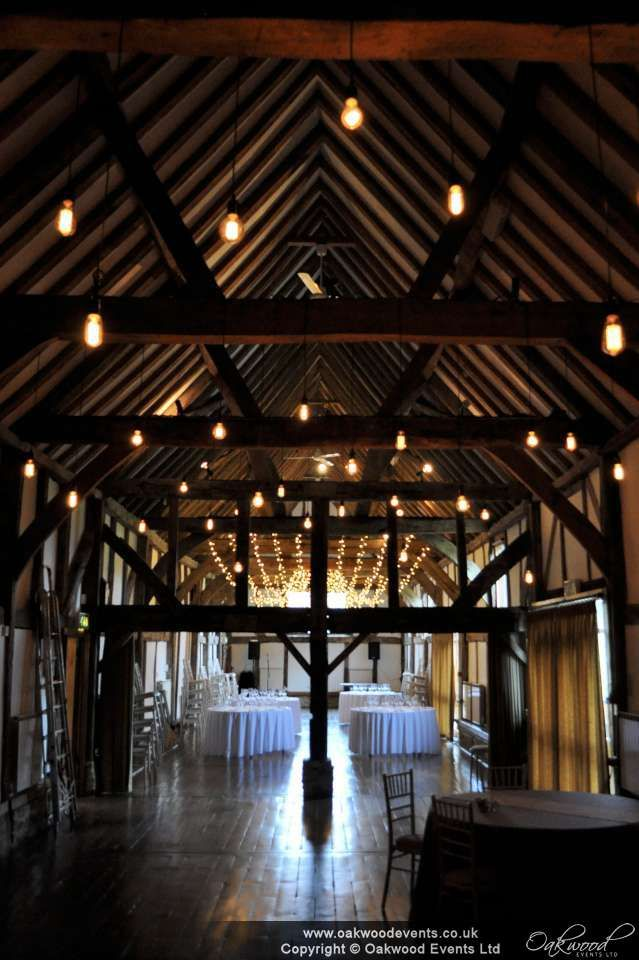 Edison bulbs with fairy lights in the back ground. The beautiful Loseley Park barn. #barn #wedding #lighting