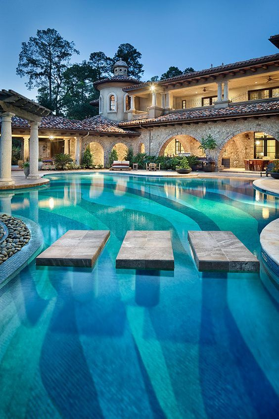 Backyard with pool of mediterranean mansion. Cool exterior and the stone facade looks gorgeous on this traditional house!