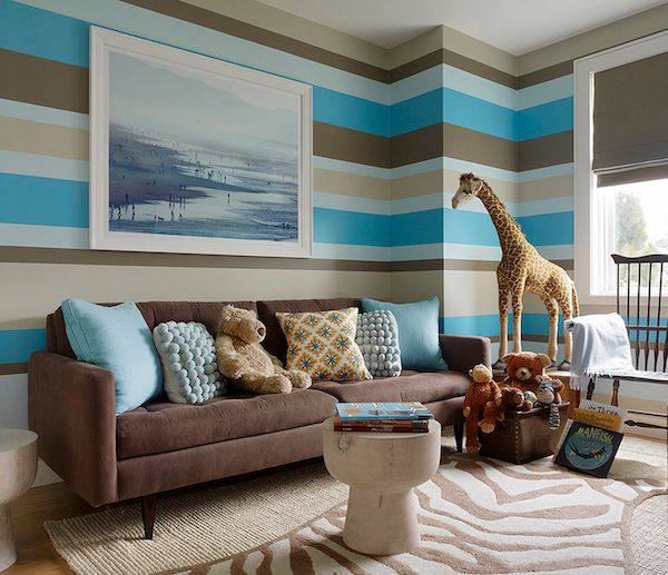 Animal-themed striped #nursery sitting area, with large giraffe and zebra #rug.