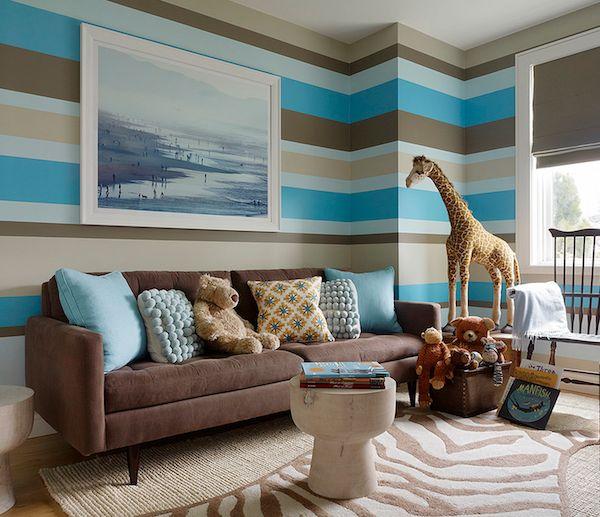 Animal-themed striped #nursery sitting area, with large giraffe and zebra #rug.