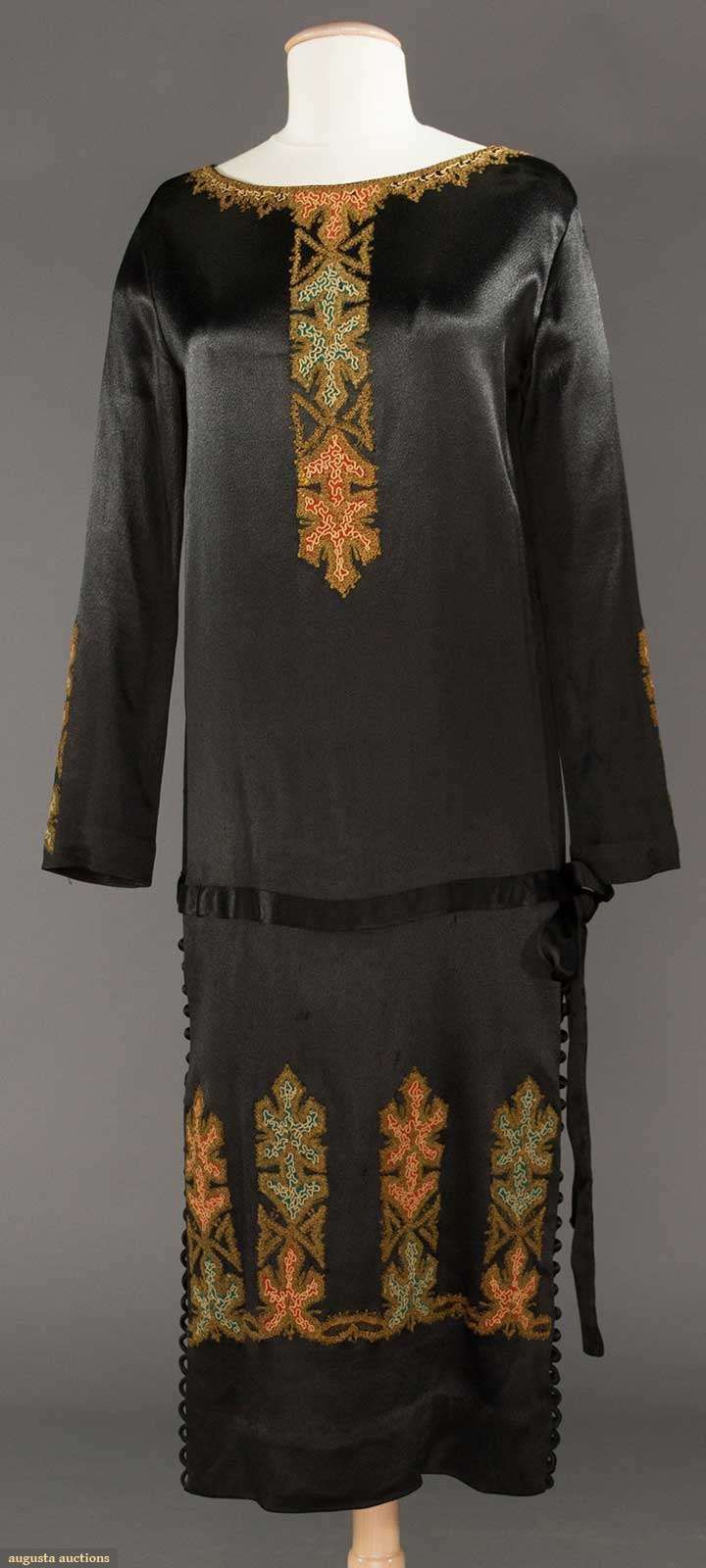 EMBROIDERED BLACK DINNER DRESS, c. 1924 Silk satin dress adorned w/ panels of stylized blossoms in orange & olive, skirt sides w/ H to hem row of self covered buttons