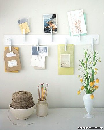 A board with clothes pegs and painted white is used to peg photos and other stuff like letters etc
