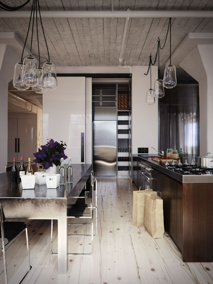 I love the play of wood vs metal in this kitchen it has a very industrial feel from the table light fixtures and chairs but adding hits of wood on the