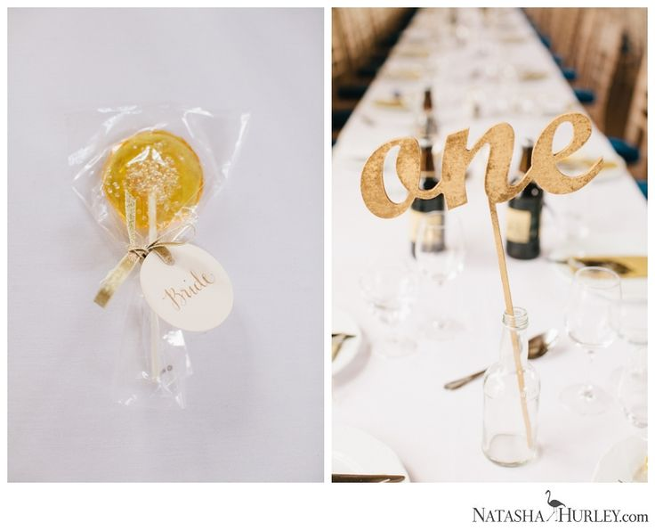 Bonhams Barn Wedding: gold wooden table numbers and glitter lollipops