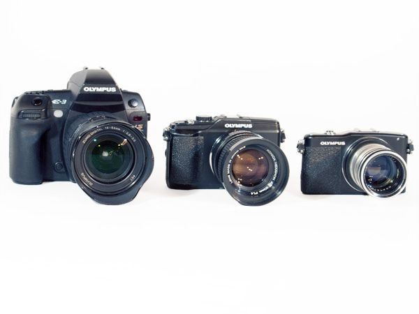 Three generation of Olympus digital system cameras, the E-3 E-Volt, E-PL2 PEN Lite, and E-PM1 PEN Mini.
