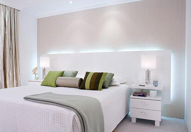 Papel de parede cinza claro bem destacado pela iluminação que sai do painel de cabeceira, bem minimalista e muito bonito! Via Casa e Jardim.