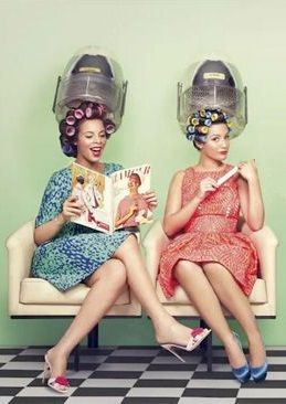 Ladies at the beauty parlor, sitting under the hair dryers.