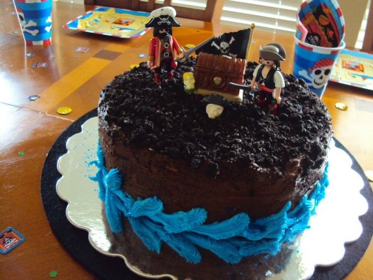 Pirate Cake - Use oreo crumbs to make dirt over chocolate frosting, get a treasure box candle and playmobil pirates. simple!!