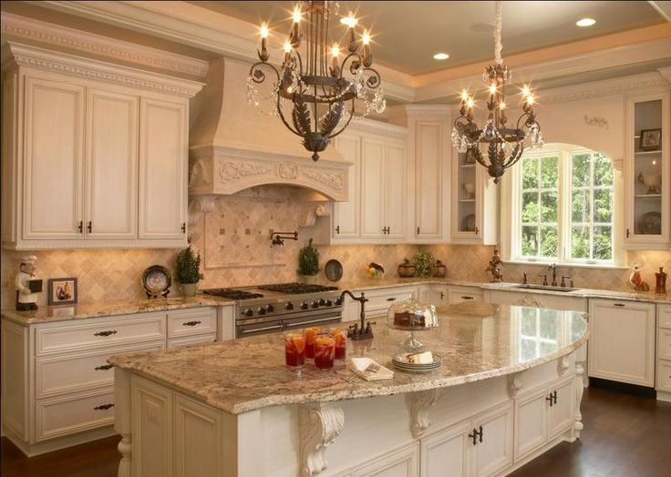 Elements of a French Country kitchen. Glazed painted cabinets. Arched window. Corbels under the island. And range hood all add to the feel and style.