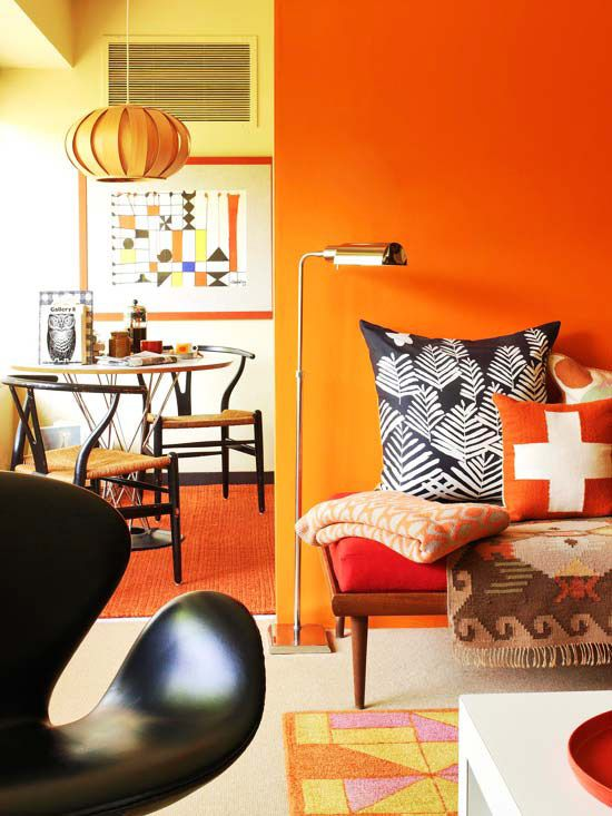 Midcentury Color Scheme: Orange + Red + Black: Give cookie-cutter architecture some identity with strong color on the walls. This wall, painted a deep orange, transforms from blank surface to architectural focal point. Splashes of orange, scattered throughout the sitting room and nearby breakfast area, integrate the color throughout the space and play off the yellow kitchen walls. The earthy colors suit the midcentury furnishings that provide the neutral foil for the bright color.