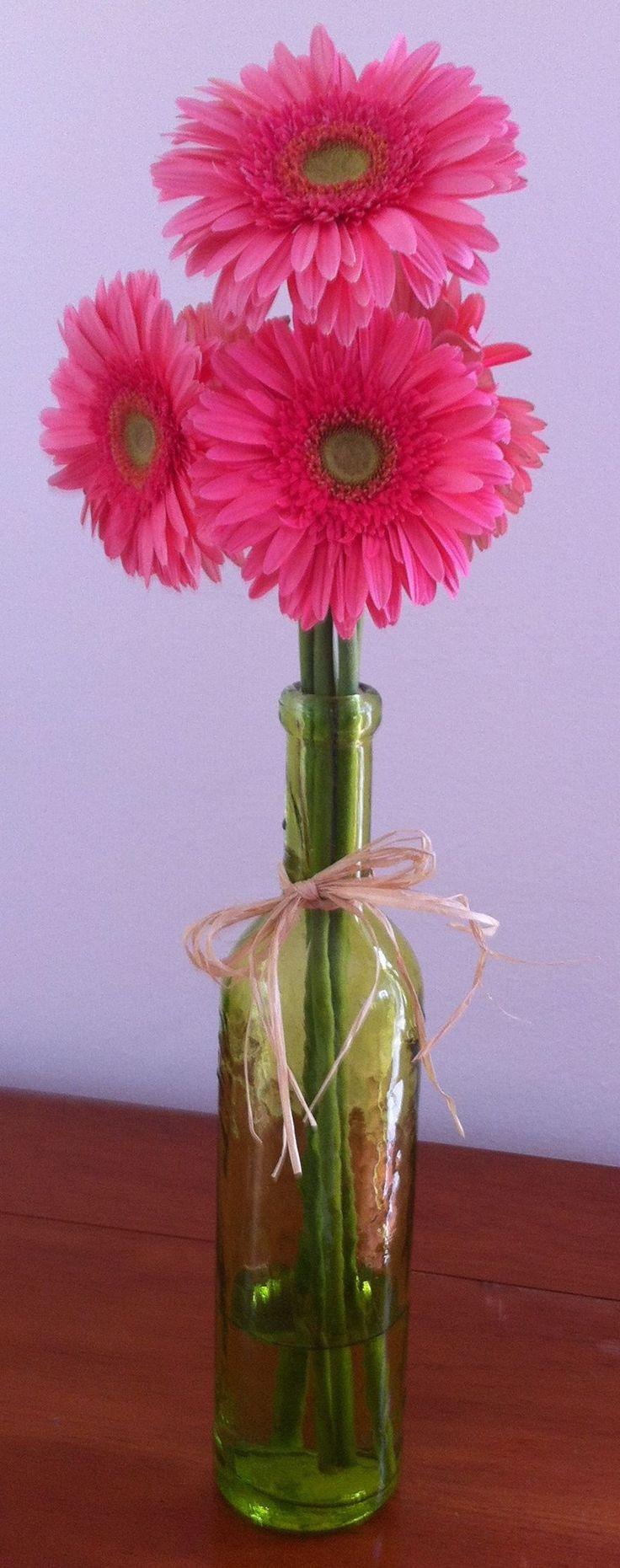 Gerberas rosas en botella verde, moño de rafia natural.