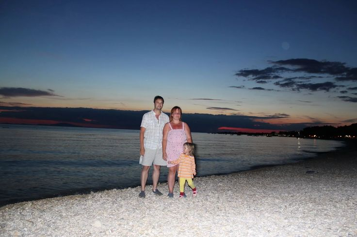 A family take an evening stroll along the coast enjoying the calm sea at the Croatian seaside resort of Pag.