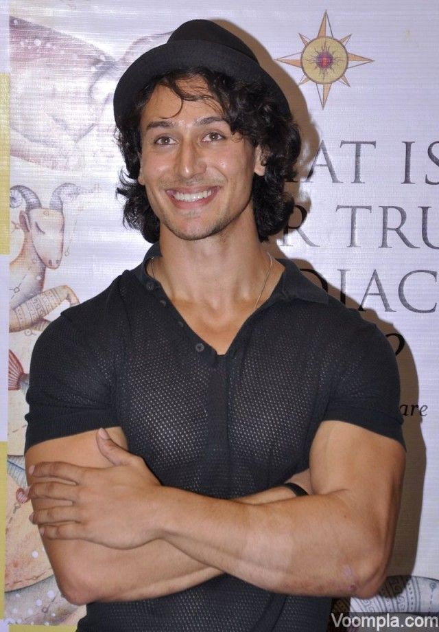 Tiger Shroff smiles while showing off his biceps, muscular arms and a toned chest in a see through top. via Voompla.com