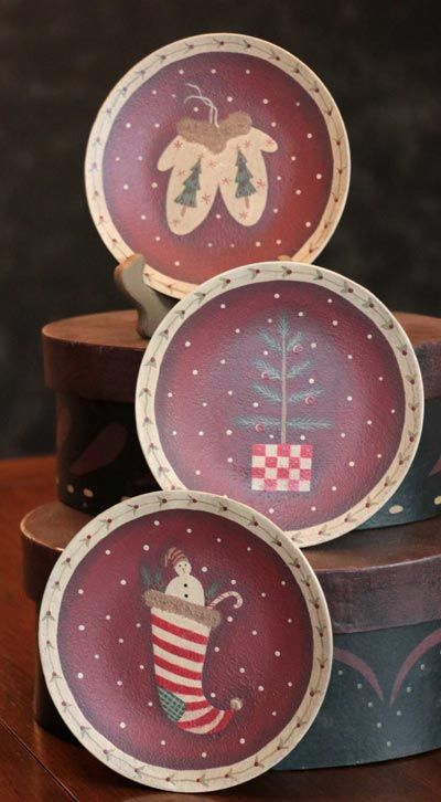 """Holiday Essentials Plates, by The Hearthside Collection. These primitive plates feature painted holiday """"essentials"""" against a burgundy background with polka dot snow. Essentials include a tree, a stocking, and a pair of mittens. Measures approx 6 inches. Made of hand-painted pressed wood, antiqued and distressed for an aged, rustic look. Decorative use only (not food ..."""