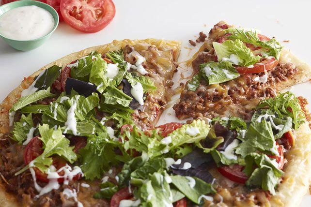Vous hésitez entre pizza, tacos et salade? Ne faites que des heureux grâce à cette pizza généreusement garnie d'un mélange pour tacos et de salade.