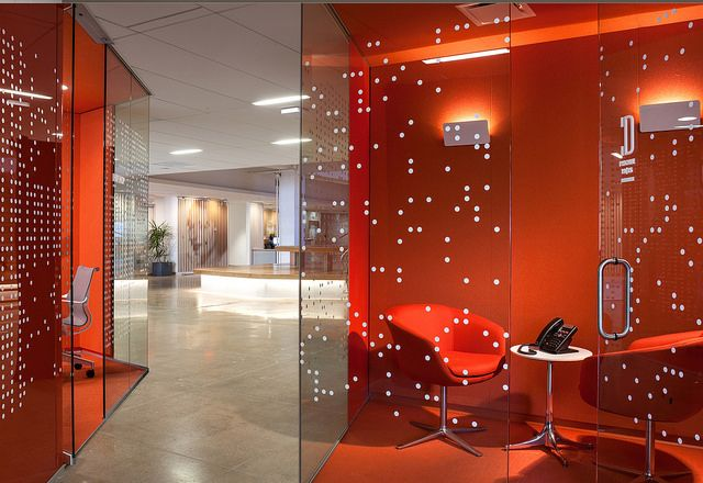 """On the north and south sides of the block-long floor plate are the open desk areas, each identified by a color and populated by faceted glass volumes that provide private meeting spaces and small """"phone booths"""" for a relief from the activity of the open areas. These """"crystals"""" invite multiple paths of movement around them, establishing a sequence of tight and loose spaces that are shaped to encourage casual interaction."""