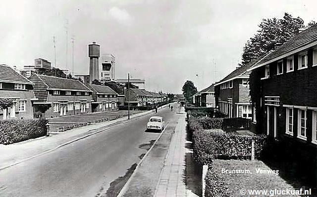 Kaart uit Brunssum, Venweg met mijnwerkershuizen met links op de achtergrond zicht op 2 schachten en de watertoren van de Hendrik. De Venweg liep langs de rechter zijkant van de Hendrik. © Bouten.