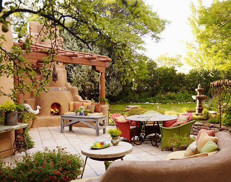 Inviting Southwestern Terrace:   Traditional Southwest décor meets contemporary design and bold colors to create this wonderful outdoor dining area in Santa Fe. Terra cotta and apricot tones warm the patio's palette, while a stone fireplace heats up the sitting area. Vibrant dining chairs and seat cushions introduce hues from the lush landscape surrounding the patio.