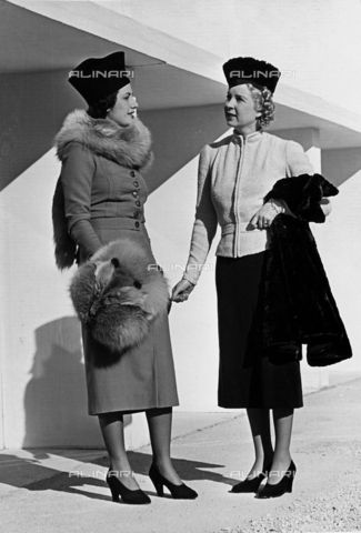 """Two models present day-wear articles created by the couture house """"Fumach"""". The model to the left wears a dress complemented by fox stole and muff. The model to the right wears a suit consisting of a short jacket and skirt.1935 - 1939(c) Bogino, Luis Fratelli Alinari Museum Collections, Florence"""