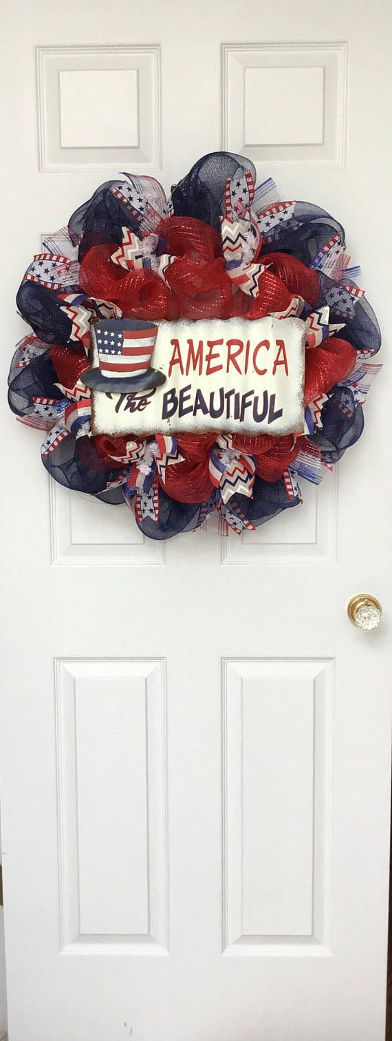 Beautiful, New, Large, Full, Premium, Handmade, Patriotic wreath. A large, rustic corrugated tin sign, rests on a bed of metallic red Deco mesh. The sign is decorated with an Uncle Sam hat and has the wording America The Beautiful. Gorgeous cream canvas patriotic chevron ribbons and