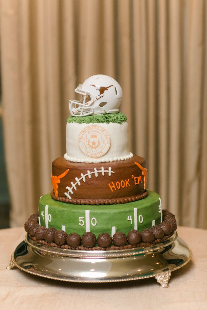 Three tiered University of Texas Longhorns football themed grooms cake lined with chocolate covered strawberries and topped with a football helmet - Photo by Arden Prucha Photography