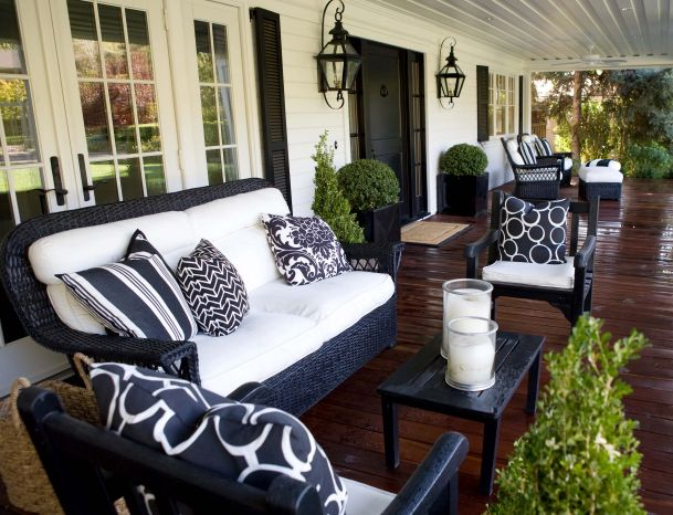 "In black and white...fab traditional porch with black wicker furniture and black and white cushions to complement the house exterior's white clapboard and black shutters and set off by gorgeous garden greenery and dramatic dark timber decking...Design Chic: The ""Light"" First Impression"