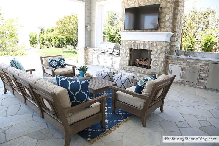 Covered patio features Restoration Hardware Leagrave Classic Lounge Chairs and Sofa lined with blue and turquoise ikat pillows facing a Leagrave Coffee Table atop a Dash & Albert rug.