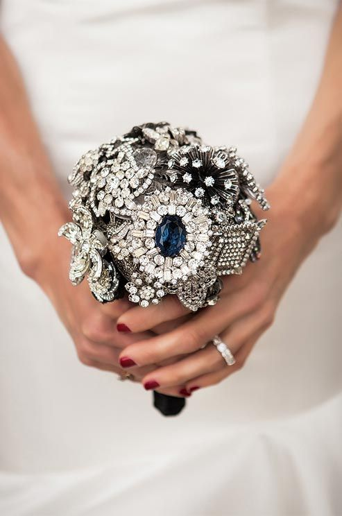 """A dramatic """"Something Blue"""" was added to the bouquet in the form of a vintage blue sapphire and diamond brooch."""