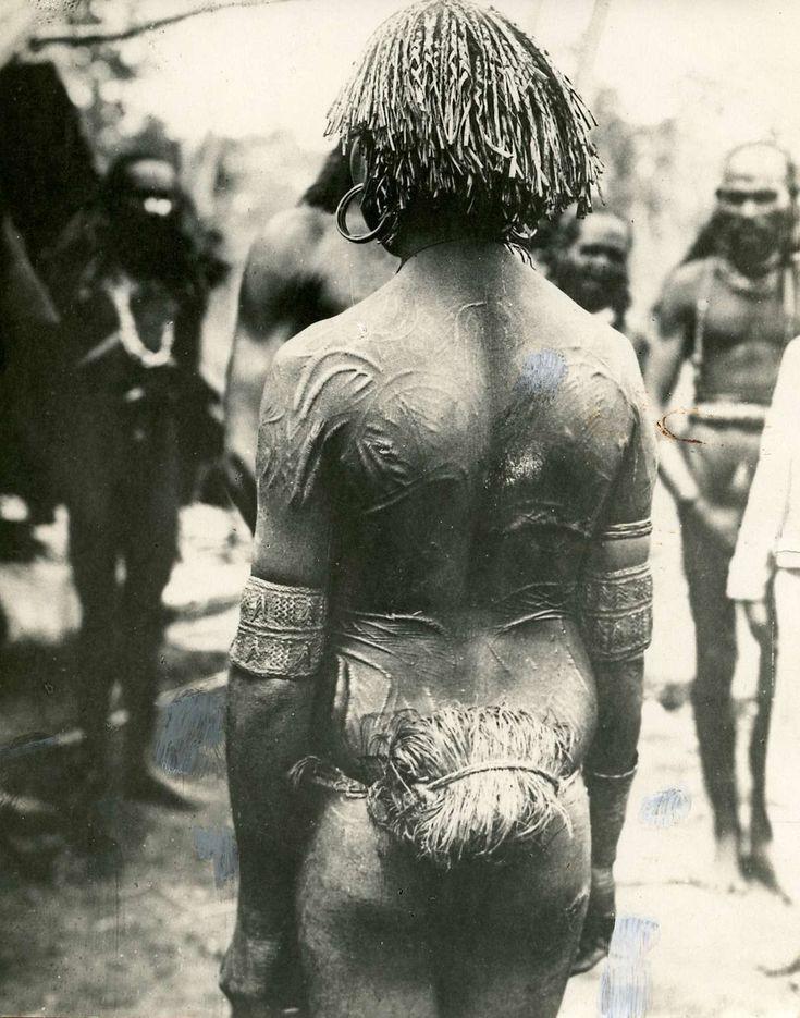 Papua : Papoea aan de Zuidkust van Nieuw Guinea op de rug gezien met diverse versieringen op zijn rug. 1927.