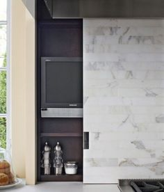 hidden tvs - small flat screen in a shallow appliance garage behind a pro-style range in a Mick De Giulio kitchen - Trad Home via Atticmag