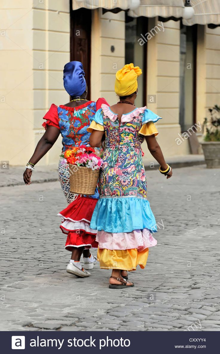 Two Creole Women Wearing Colourful Dresses Walking In The Centre