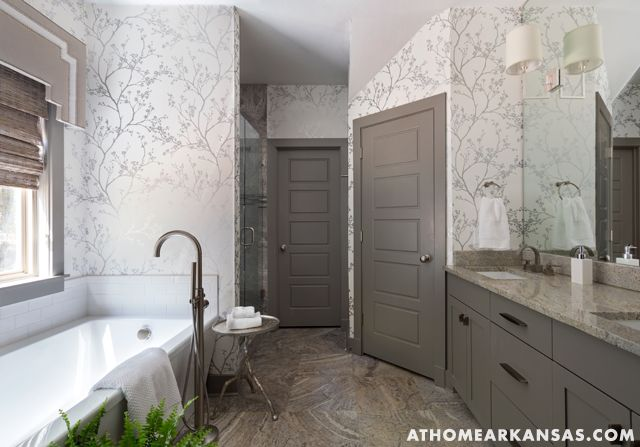 At Home in Arkansas   July 2014   Nautical Escape   Photography: @nancynolan The bathroom's cabinets are painted the same color as the trim throughout the house (Sherwin-Williams' Dovetail), which coordinates nicely with the silver travertine tile. Sconces from Circa Lighting and metallic wallpaper from Schumacher give the space a decidedly grown-up feel.