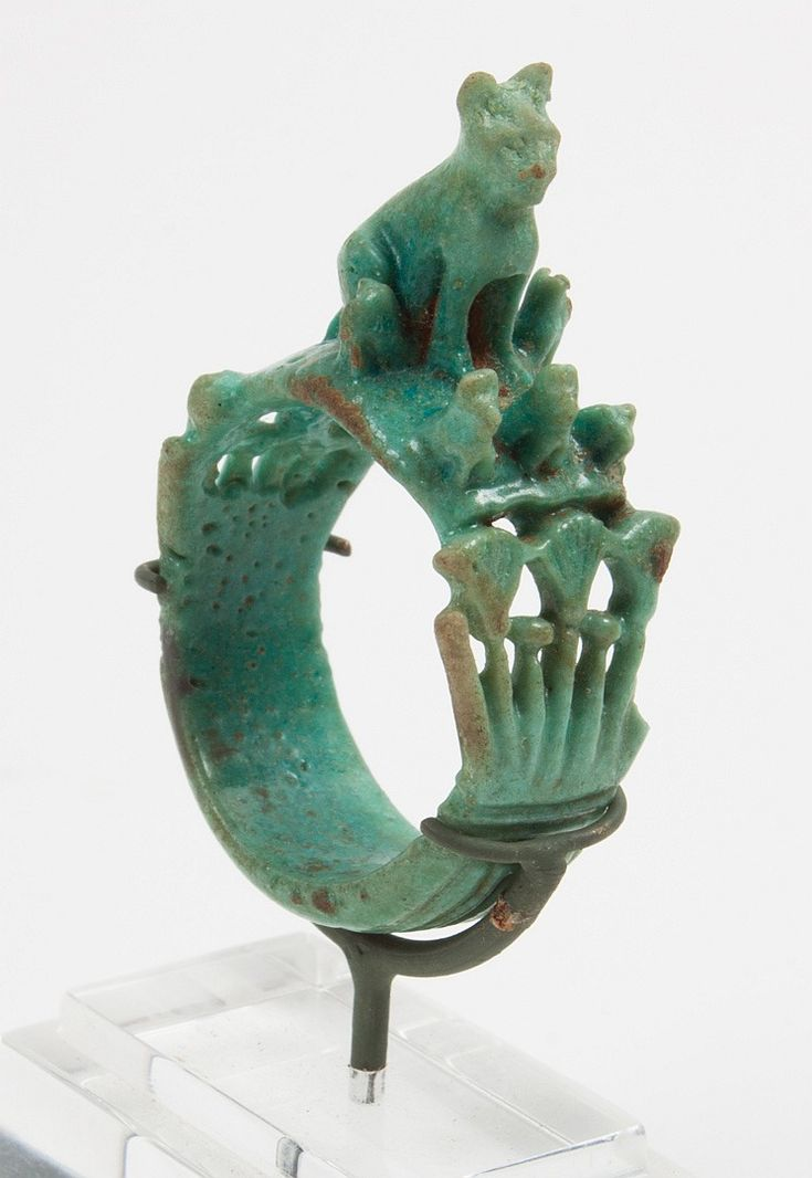 Rare ancient Egyptian faience figural ring; deep greenish blue faience ring, New Kingdom, 18th-19th Dynasty, the table modeled with a large seated cat (Bastet) surrounded by smaller cats, intricately detailed