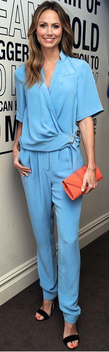 Blue long sleeve pleated jumpsuit and orange clutch handbag