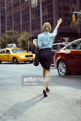 Stock Photo : Caucasian woman hailing taxi in urban street