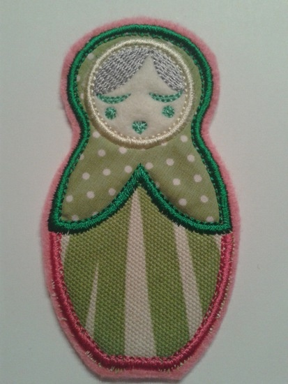 Deze leuke Anoushka Babushka applicatie in roze-groen is ongeveer 10 centimeter