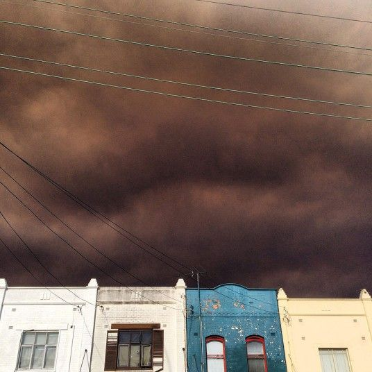 Thick black smoke from a bushfire billows over houses at South King Street in Newtown, Australia