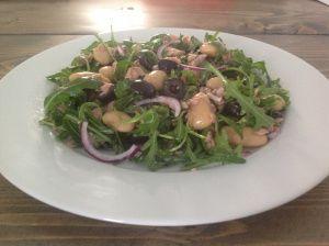 Rucola-Tonijn Lunchsalade met bonen - 160 gr witte reuzen bonen (1 klein blikje) 60 gr tonijnstukken in olijfolie (1 klein blikje) halve rode ui twee eetlepels zwarte olijven in schijfjes 35 gr rucola, honing mosterd dressing