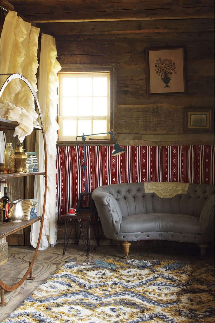 Anthropologie living room - Anthropologie Home Decor Settee And Colorful Rug Wood Panel Walls
