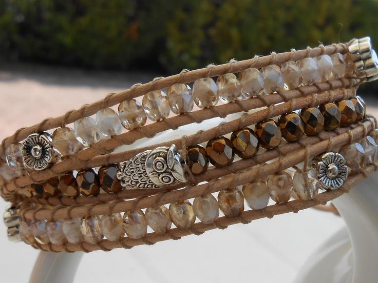 Tre giri in mezzi cristalli color oro brunito e champagne, cuoio neutro e distanziali color argento.