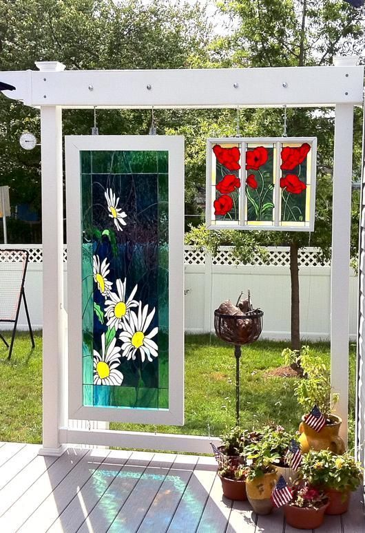 Stained Glass Windows Displayed On Garden Arbors By A Deck