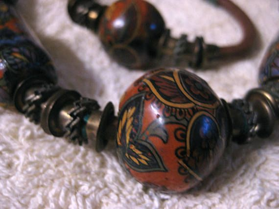 Beautiful example of 1970s style. Ceramic, Paisley decorated beads , married with thick suede and brass fittings for an earthy bohemian look. Wrapped wire closures on both choker and bracelet. Choker is 15.5 inches long, Bracelet is 8 inches.  These great ceramic beads are heavy,
