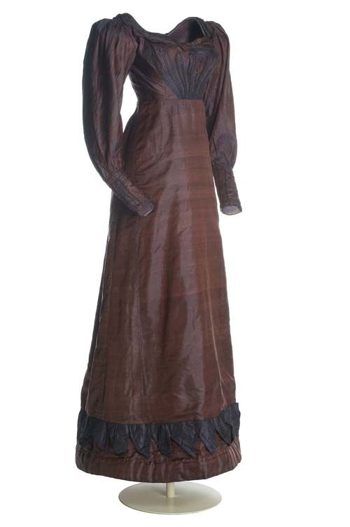 [via google translate] Romanticism, ca. 1817-1820 Taffeta Dress in eggplant. With boat neckline and waist below the chest. Sleeve, long puffed on his arm. The entire bottom perimeter of the skirt is decorated with a blue fabric application capped peak. MT097660 is an excellent example of the dresses that start the first romantic style, in which the detail is approaching its natural site and sleeves start to abullonarse in the arm. Museo del Traje.