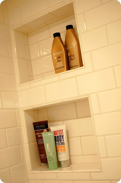 Add a stainless steel bar across each opening so that the shelf can be slightly slanted for drainage. No standing water to eat at your grout and less cleaning.   :)