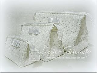 Arte Em Fuxico e Cia: Trio Necessaire Triangular Em cambraia de algodão e bordado inglês (Lateral) Detalhe de lacinho Chanel em fita de cetim e organza. Parte interior em tecido branco 100% algodão, plastificada. Dimensões: Grande: 31 X 19 X 13 cm Média: 22 X 15 X 11 cm Pequena: 15 X 10 X 8 cm