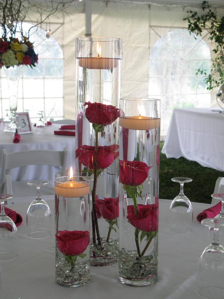 This bride wanted to use a variety of jewel-toned colors in her floral material. We accommodated her request with deep blue and white hydrangeas, hot pink and yellow roses, hot pink gerber daisies, pink alstroemeria, white lilies, yellow calla lilies, topped with curly willow. Then we complemented the main centerpieces with other table settings of hot pink roses sunk in water on top of a foundation of clear glass stones topped with floating candles.